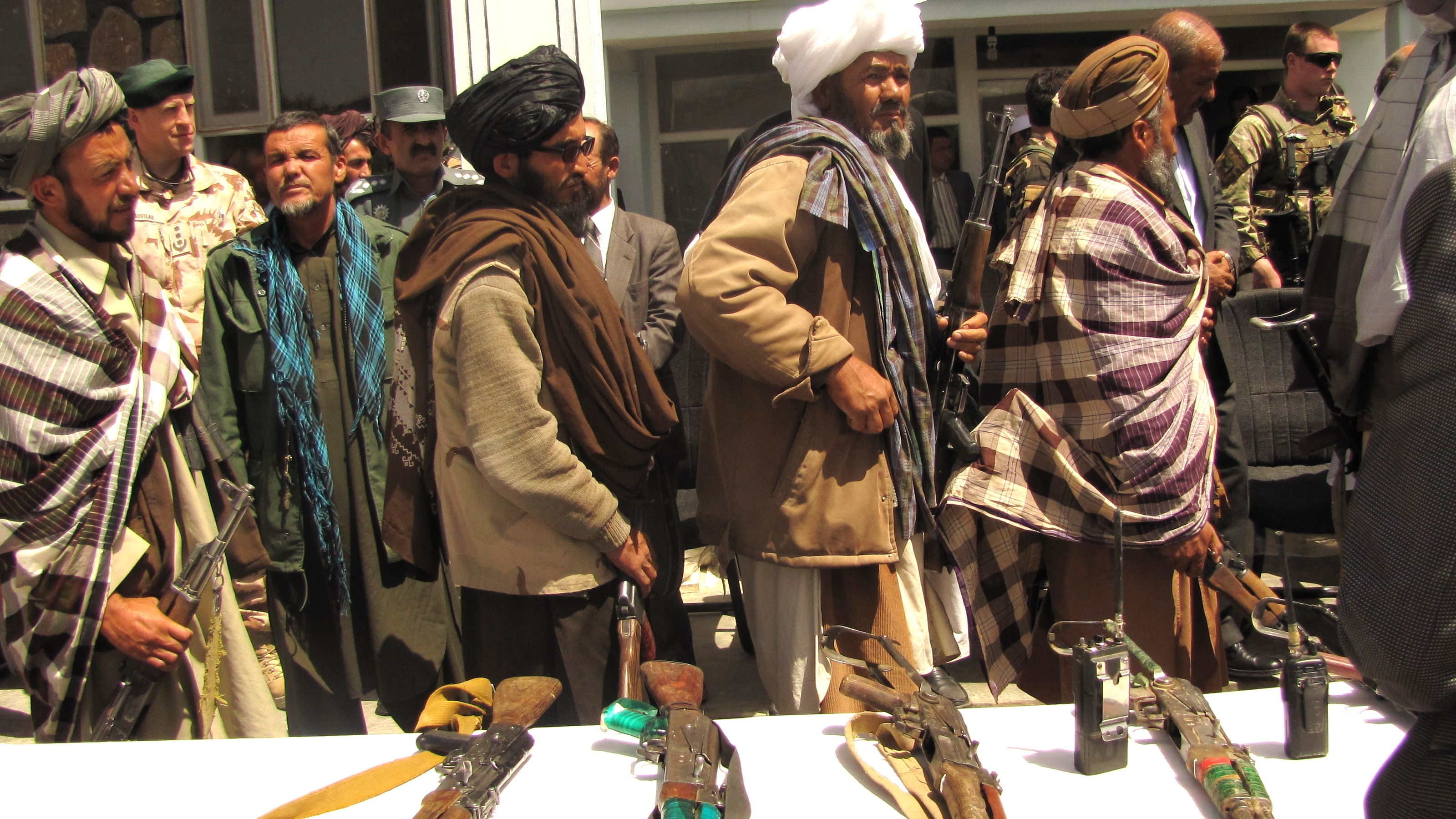 Taliban fghters surrendering and letting go of weapons.