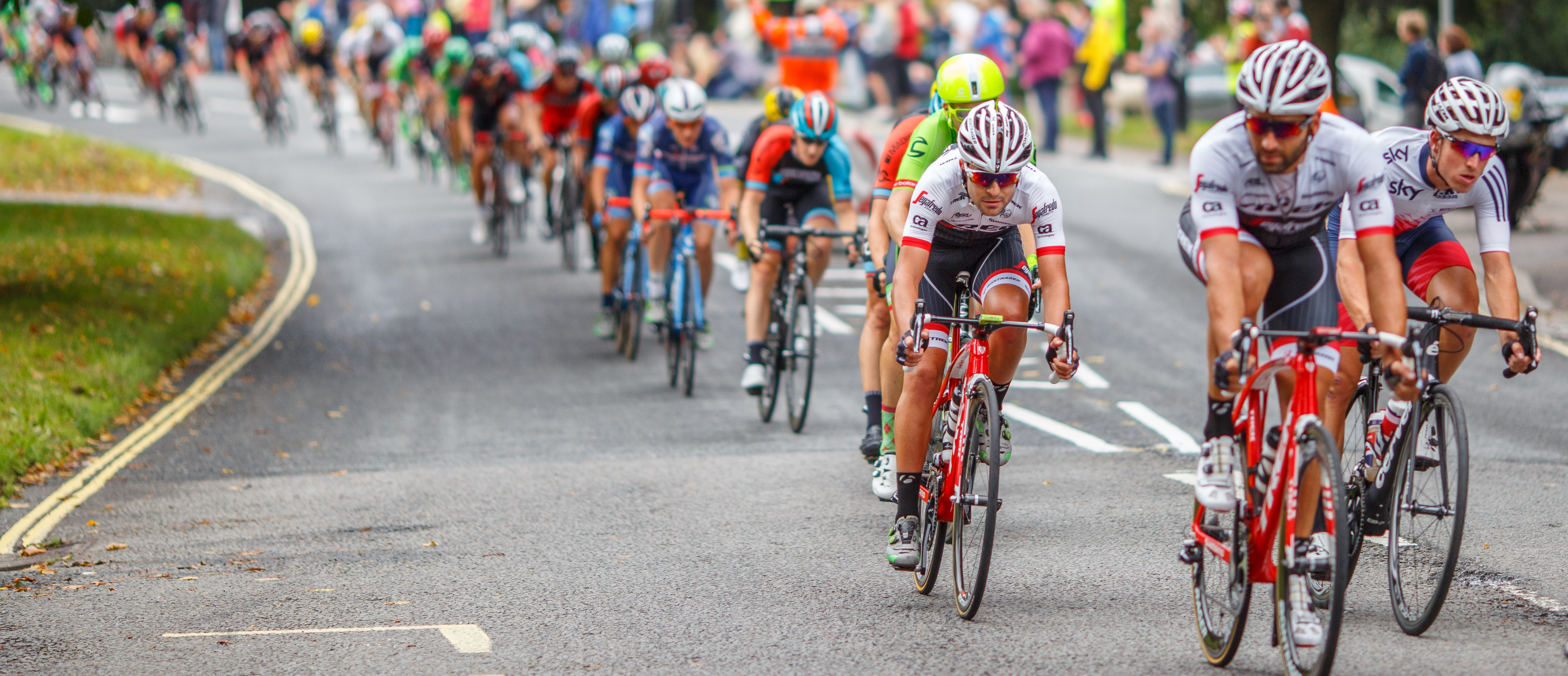 Peloton; picture of a bike race. Hundreds of people on bikes with colorful helmets and bikes.